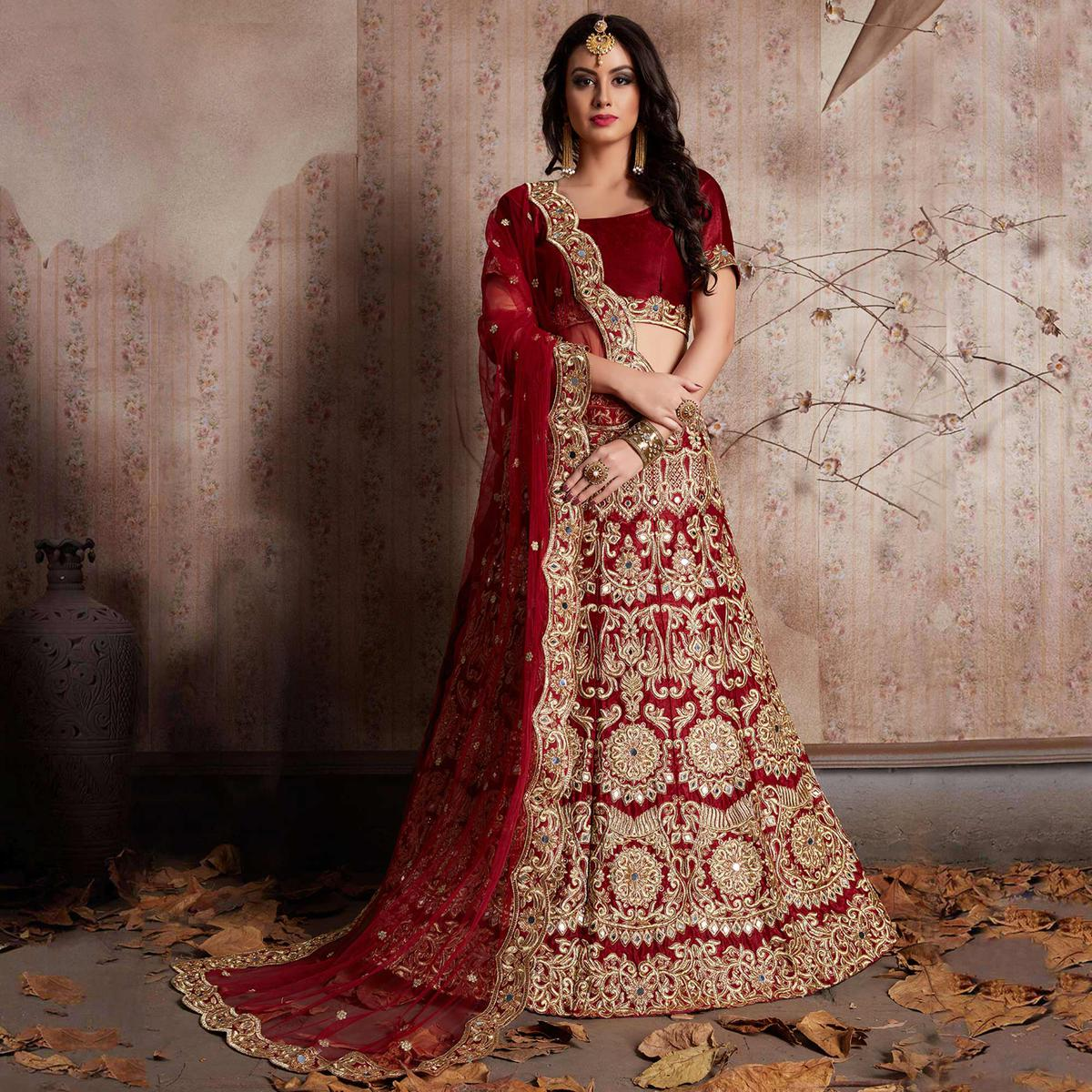 Glowing Maroon Colored Party Wear Designer Embroidered Velvet Silk Lehenga Choli