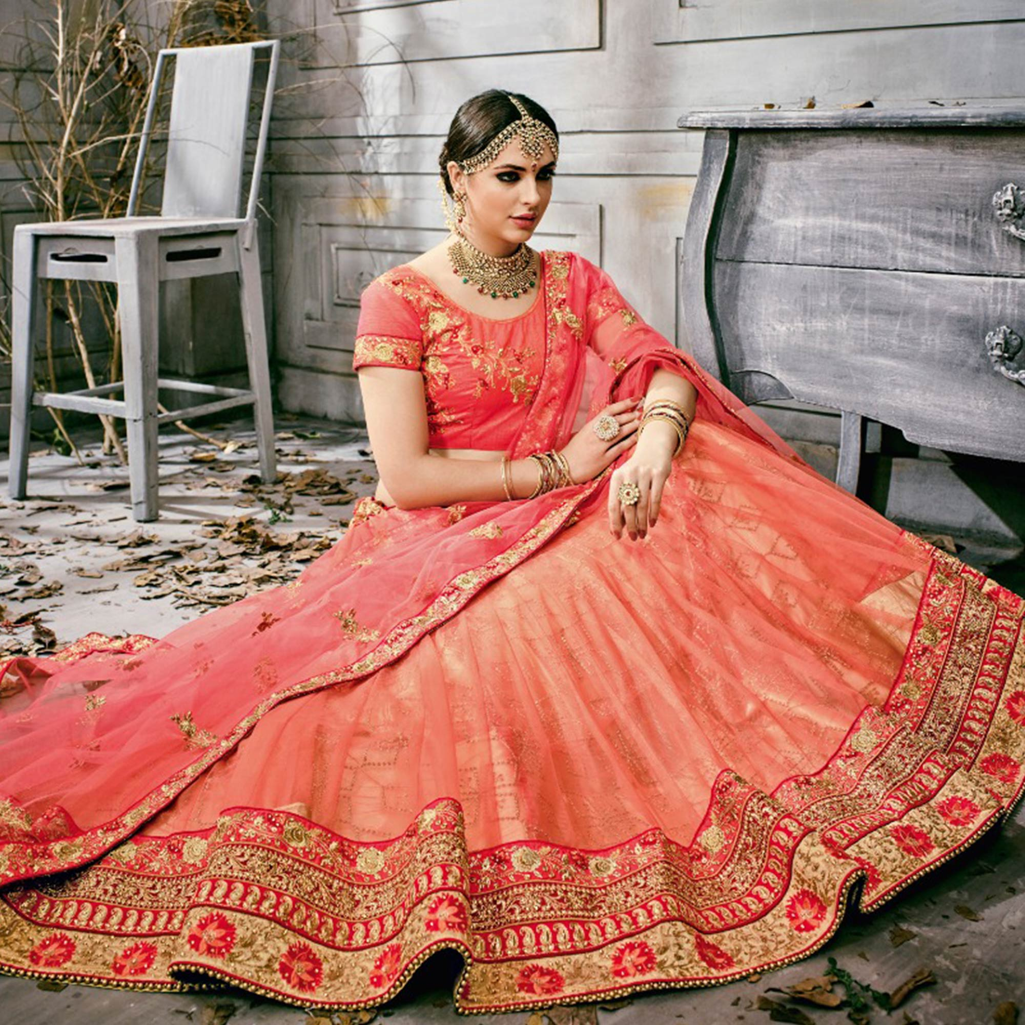 Gorgeous Peach Colored Partywear Embroidered Netted Lehenga Choli