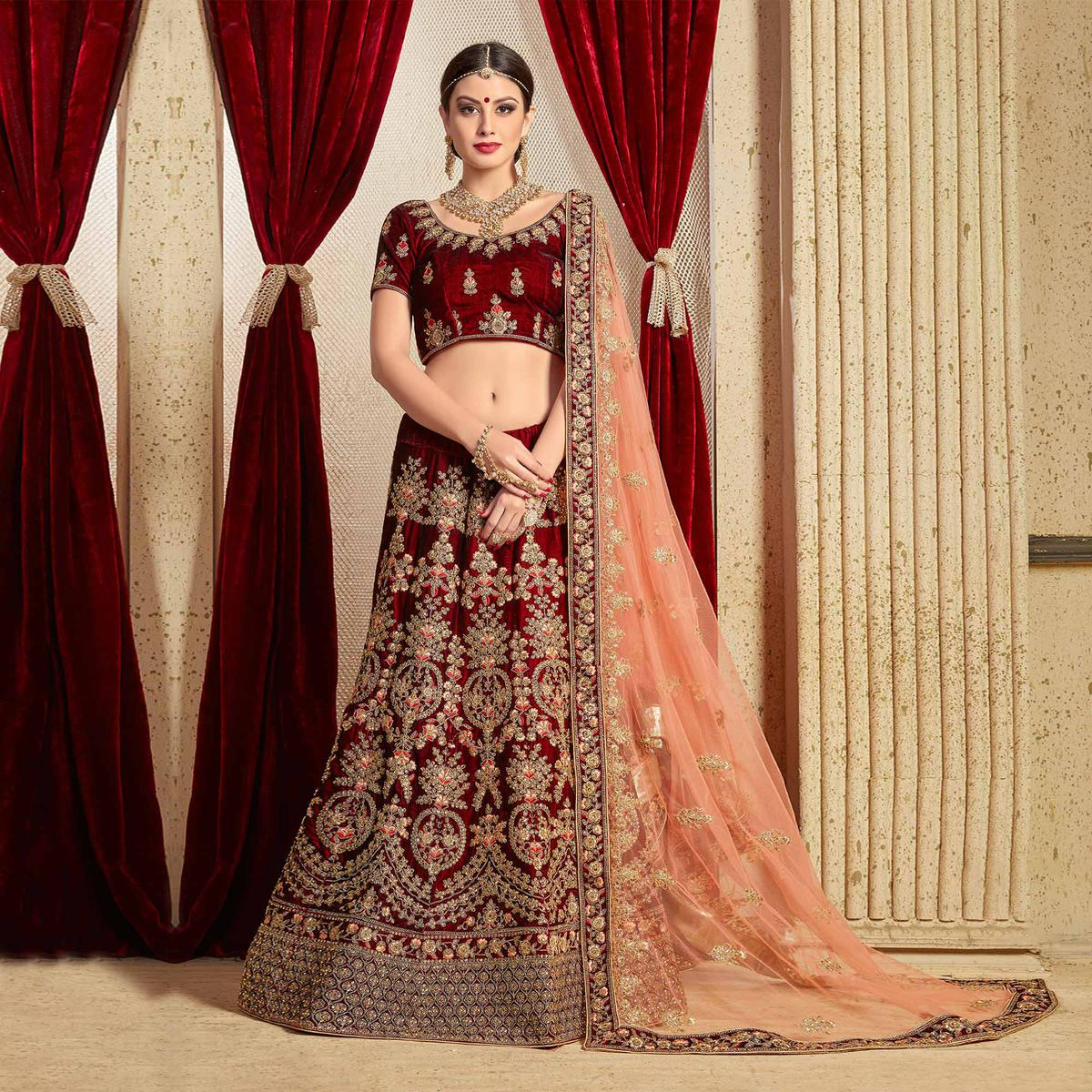 Hypnotic Maroon Colored Partywear Embroidered Pure Velvet Lehenga Choli