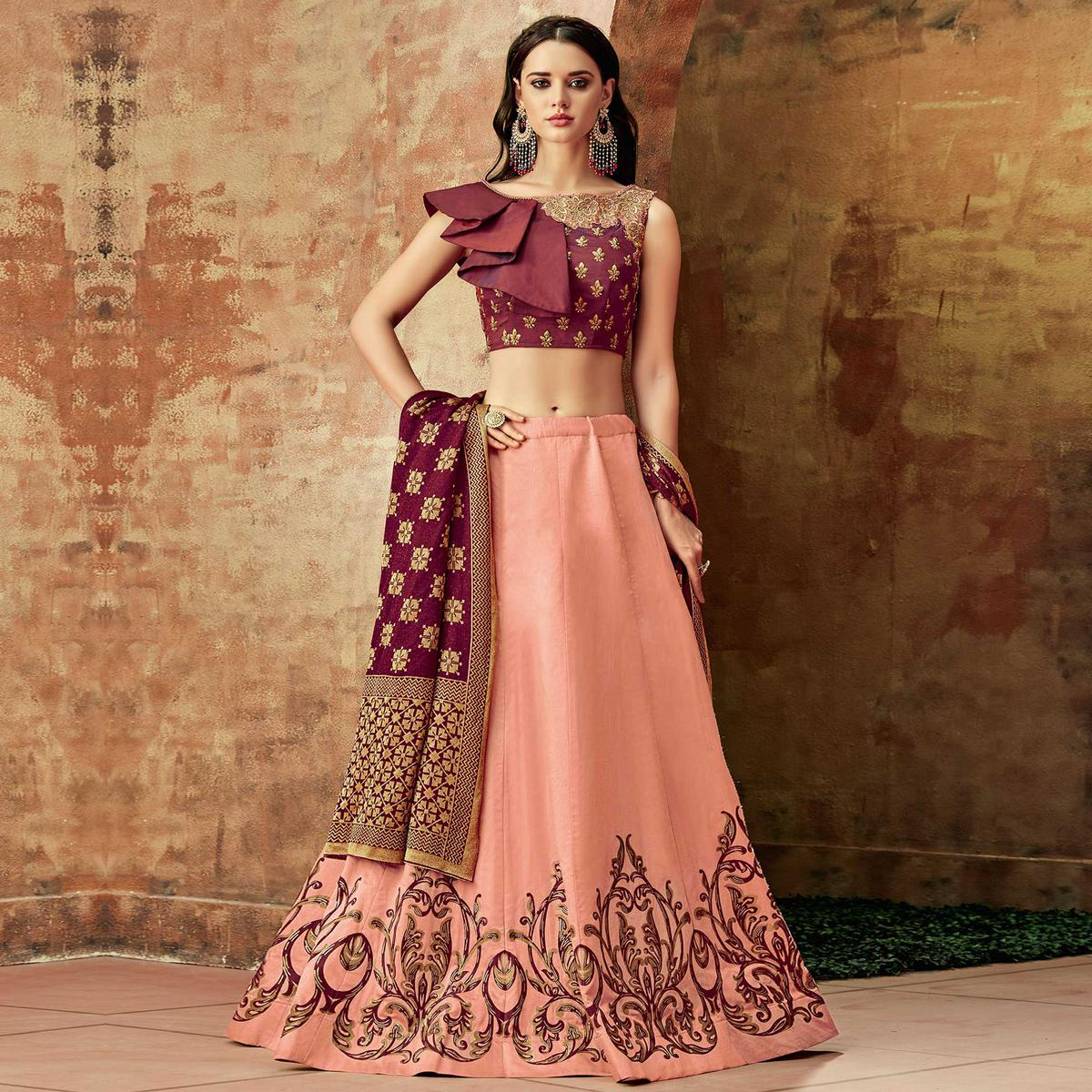 Dazzling Peach Colored Partywear Embroidered Silk Lehenga Choli