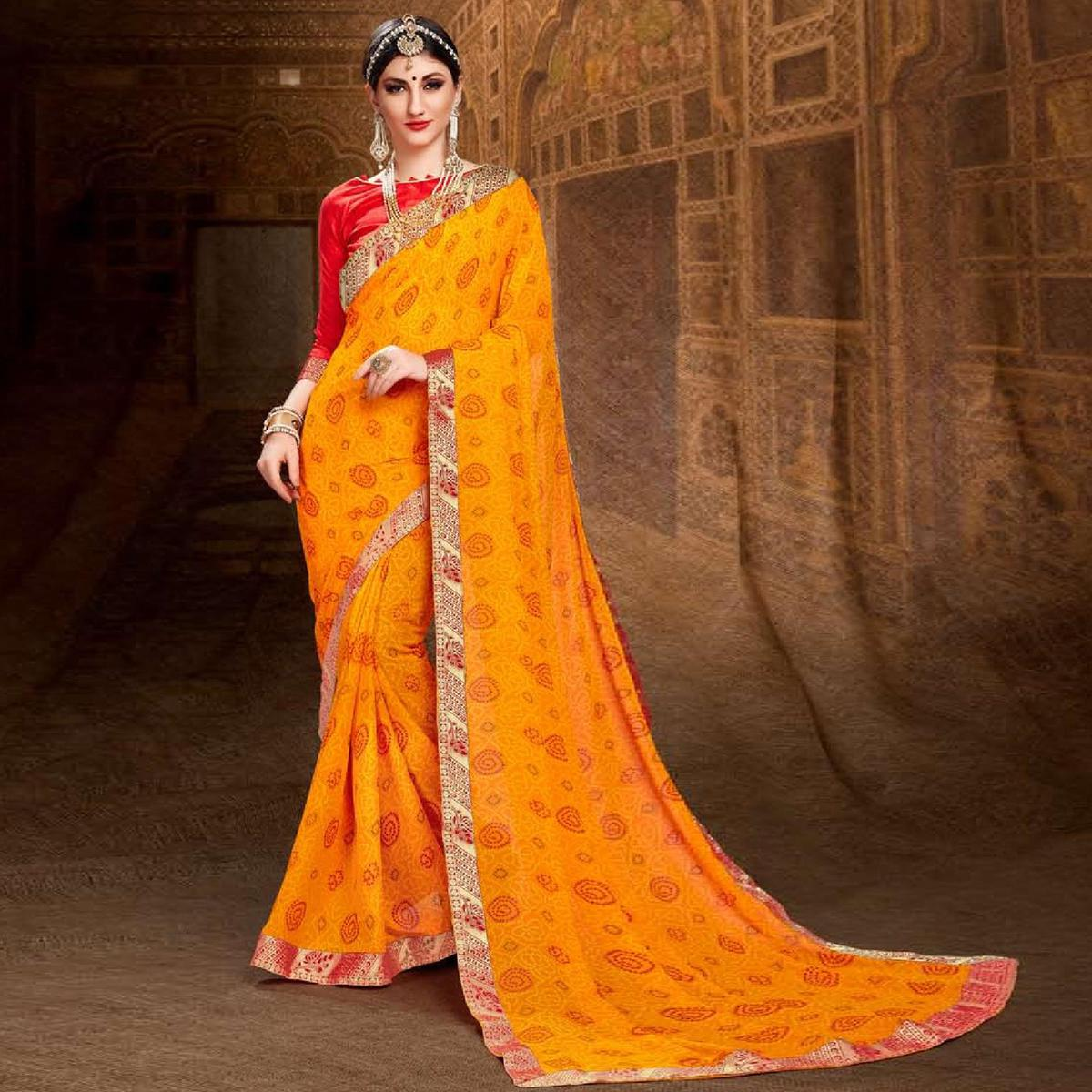 Glowing Orange Colored Bandhani Printed Heavy Georgette Saree With Jacquard Lace Border