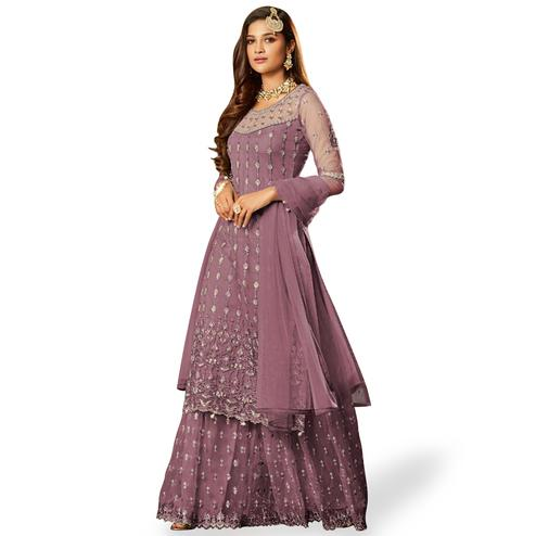 Hypnotic Deep Mauve Colored Partywear Embroidered Net Lehenga Kameez