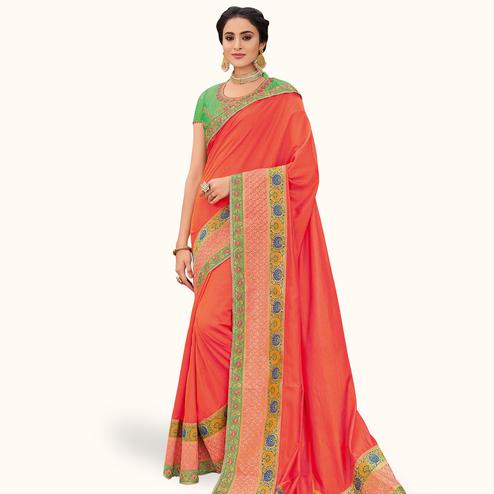Radiant Orange Colored Partywear Embroidered Raw Silk Saree