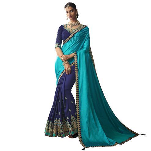 Magnetic Blue Colored Partywear Embroidered Raw Silk Saree