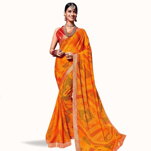 Lovely Orange Colored Bandhani Printed Heavy Georgette Saree With Jacquard Lace Border