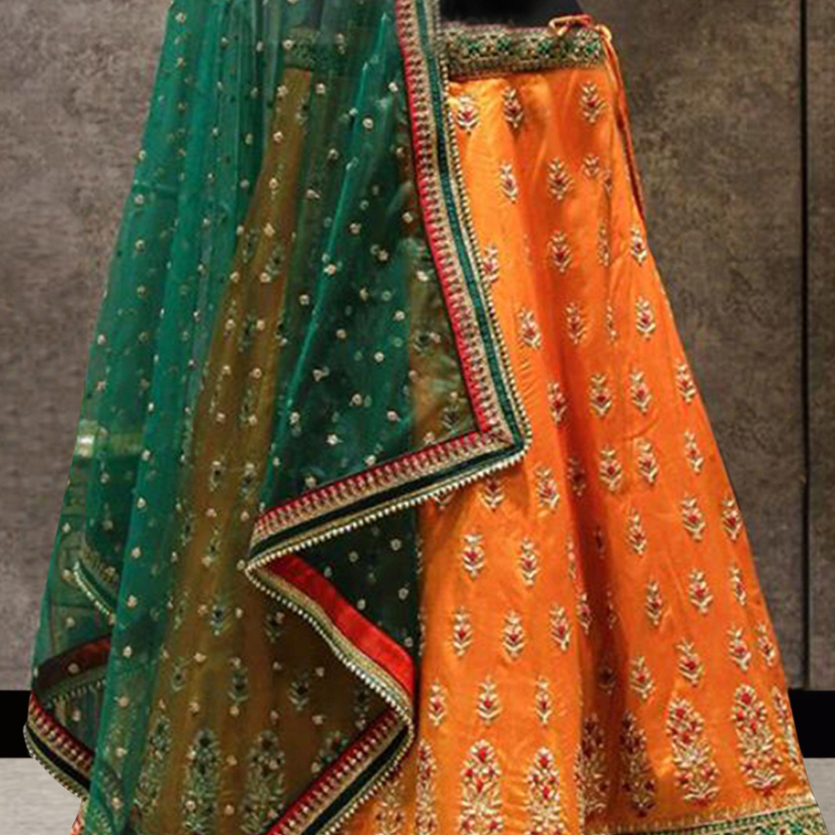 Unique Orange Colored Partywear Embroidered Raw Silk Lehenga Choli