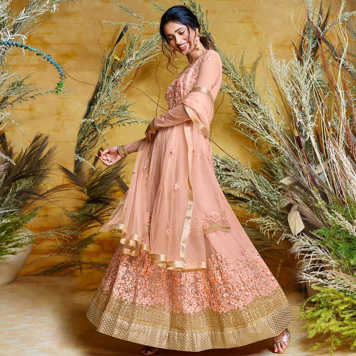 Captivating Peach Colored Partywear Embroidered Net Gown