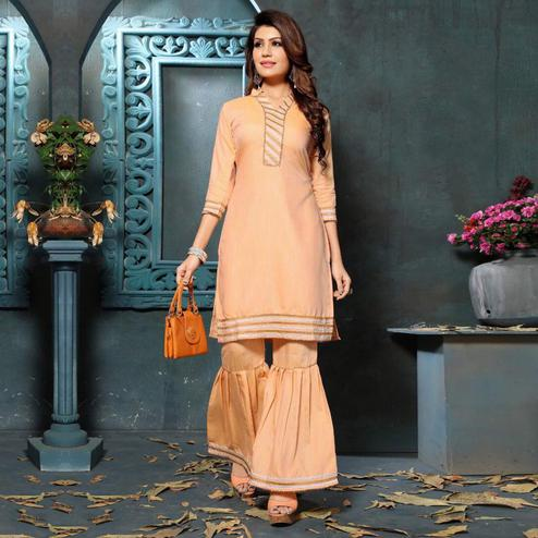 Adorning Peach Colored Partywear Cotton Kurti-Sharara Set
