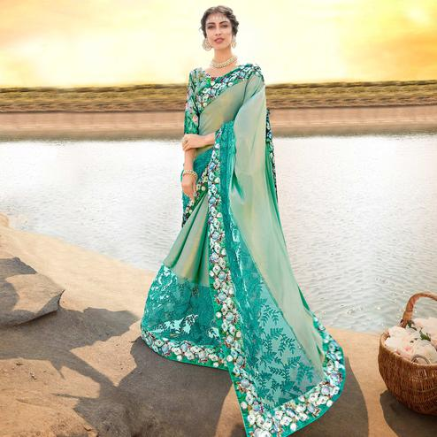 Alluring Aqua Green Colored Partywear Printed Lycra & Net Saree