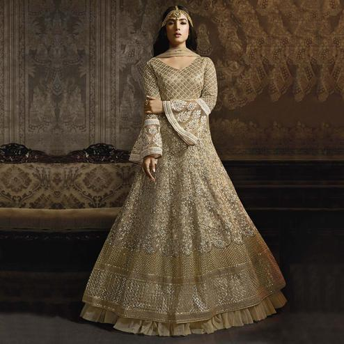 Radiant Beige Colored Partywear Embroidered Bell Sleeve Net Anarkali Suit
