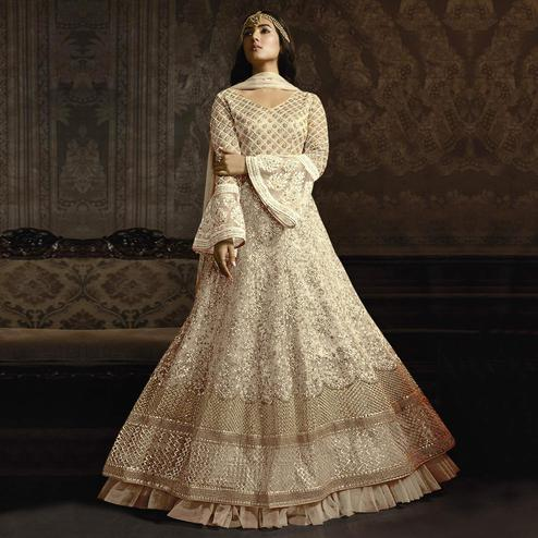 Gleaming Cream Colored Partywear Embroidered Bell Sleeve Net Anarkali Suit