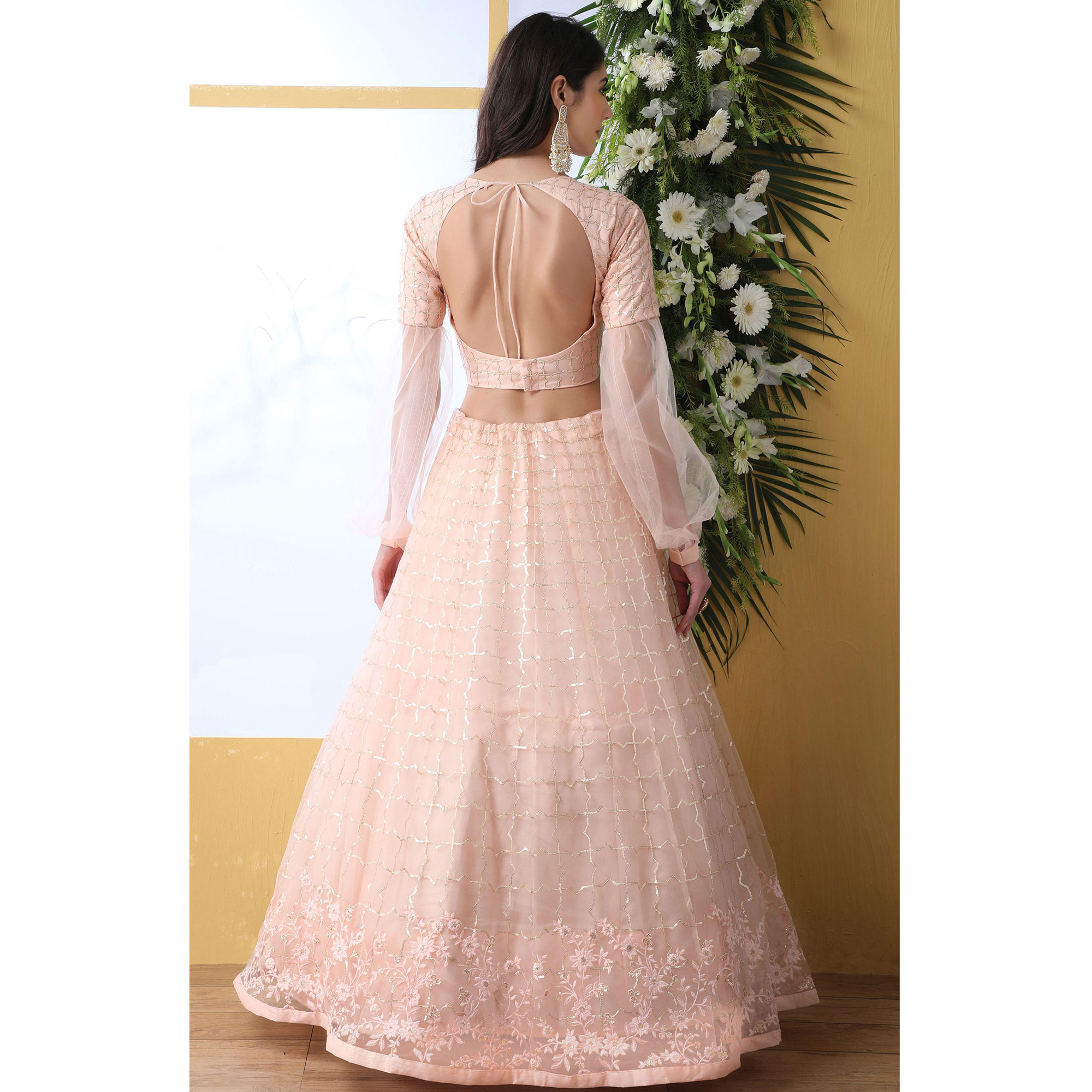 Appealing Light Peach Colored Partywear Embroidered Netted Lehenga Choli