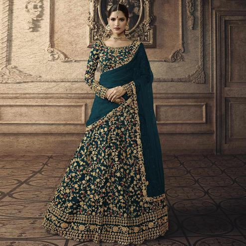 Captivating Teal Blue Colored Partywear Embroidered Net Lehenga Choli