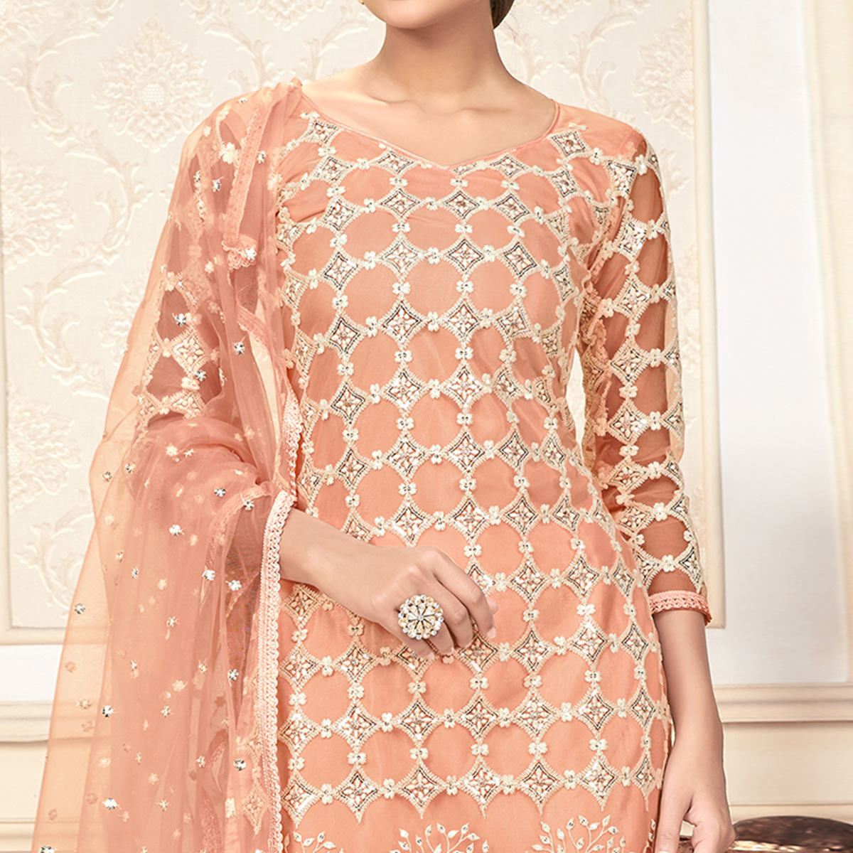 Captivating Pastel Peach Colored Partywear Embroidered Net Dress Material