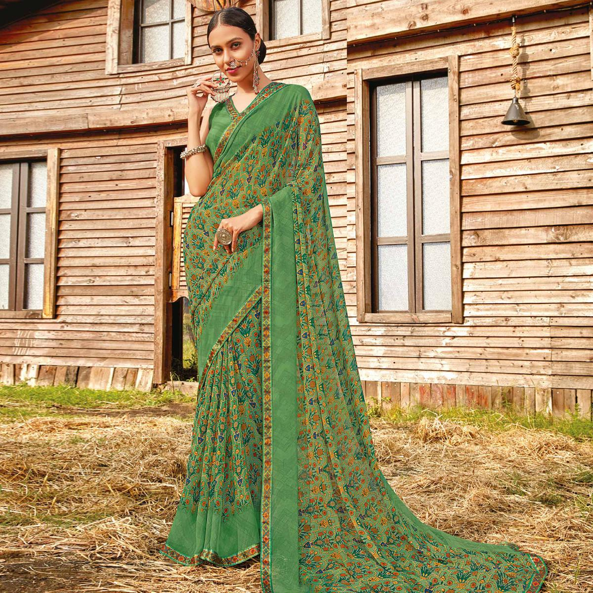 Glorious Dusty Green Coloured Partywear Pure Georgette Floral Printed Saree With Fancy Lace Border