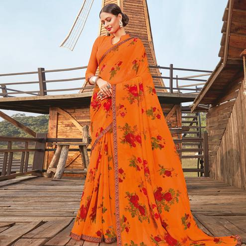 Lovely Orange Coloured Partywear Pure Georgette Floral Printed Saree With Fancy Lace Border