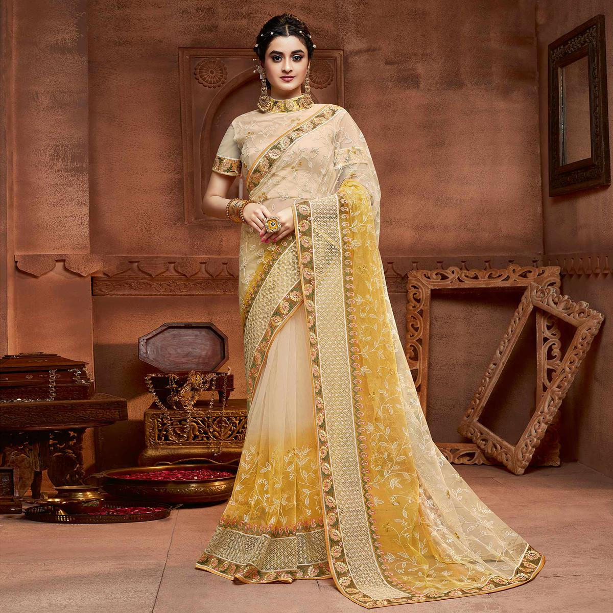 Capricious Beige & Mustard Coloured Partywear Embroidered Soft Net Saree